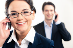 In the photo there is a man and a woman both on the telephone, looking happy and engaged in their job interview.