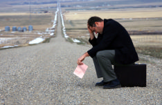 the photo shows a miserable job seeker with a pink 'end of employement' slip, worried as he doesn't know where his career path is going to take him next.